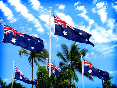 Half a dozen Australian flags flying cheerily in breeze; palm trees nearby