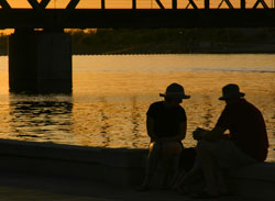 Couple silhouetted at sunset near bridge