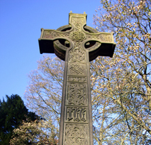 Celtic Cross in spring sunlight surrounded by trees