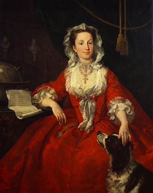 Portrait of Mary Edwards in red dress with dog; she is smiling