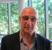 David Malouf, writer, with green trees behind him
