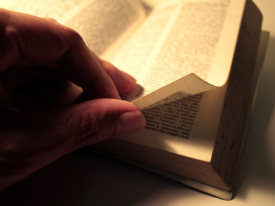 A man turns the pages of a Bible as he reads
