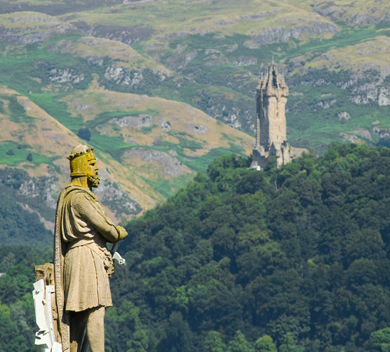 Statue of Robert the Bruce overlooking castle and wild country