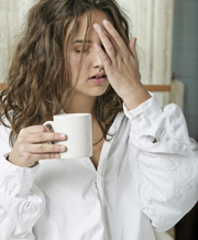 Woman dressed in white cotton shift holds her head and coffee cup