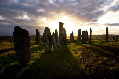 Ancient monument of standing stones cast shadows as sun rises