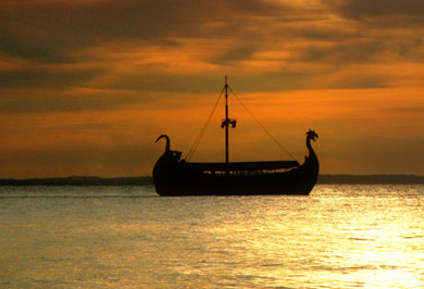 A Viking ship with curving dragon prow is silhouetted on the red-gold waters of sunset