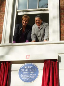 Two women leaning out a window above a Mary Seacole plaque
