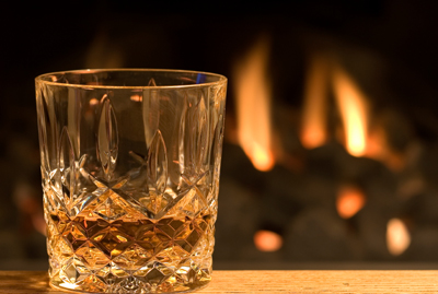 Glass of whisky before fire in hearth