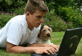 Boy with laptop and dog in garden