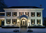 house in snow with lamps lit