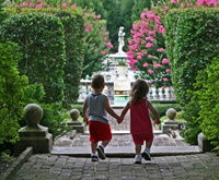 Two children walking hand in hand into a garden