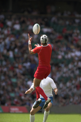 Rugby player leaps to catch ball