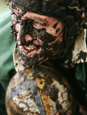 Smiling rugby player covered in mud