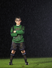 Young muddy soccer goalie in rain